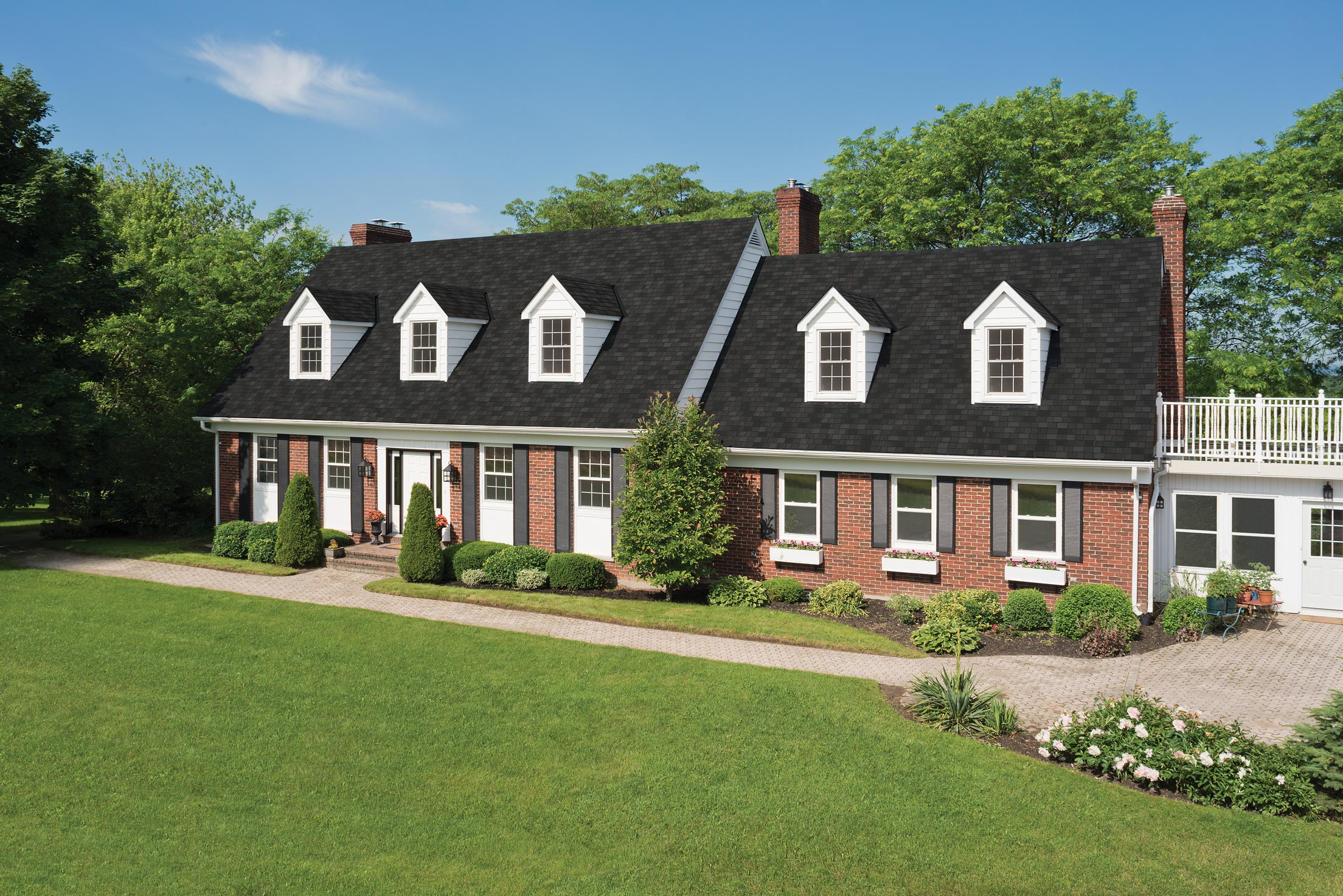 Terra Cotta brick house on a manicured lawn with Royal Estate Shadow Slate Shingles